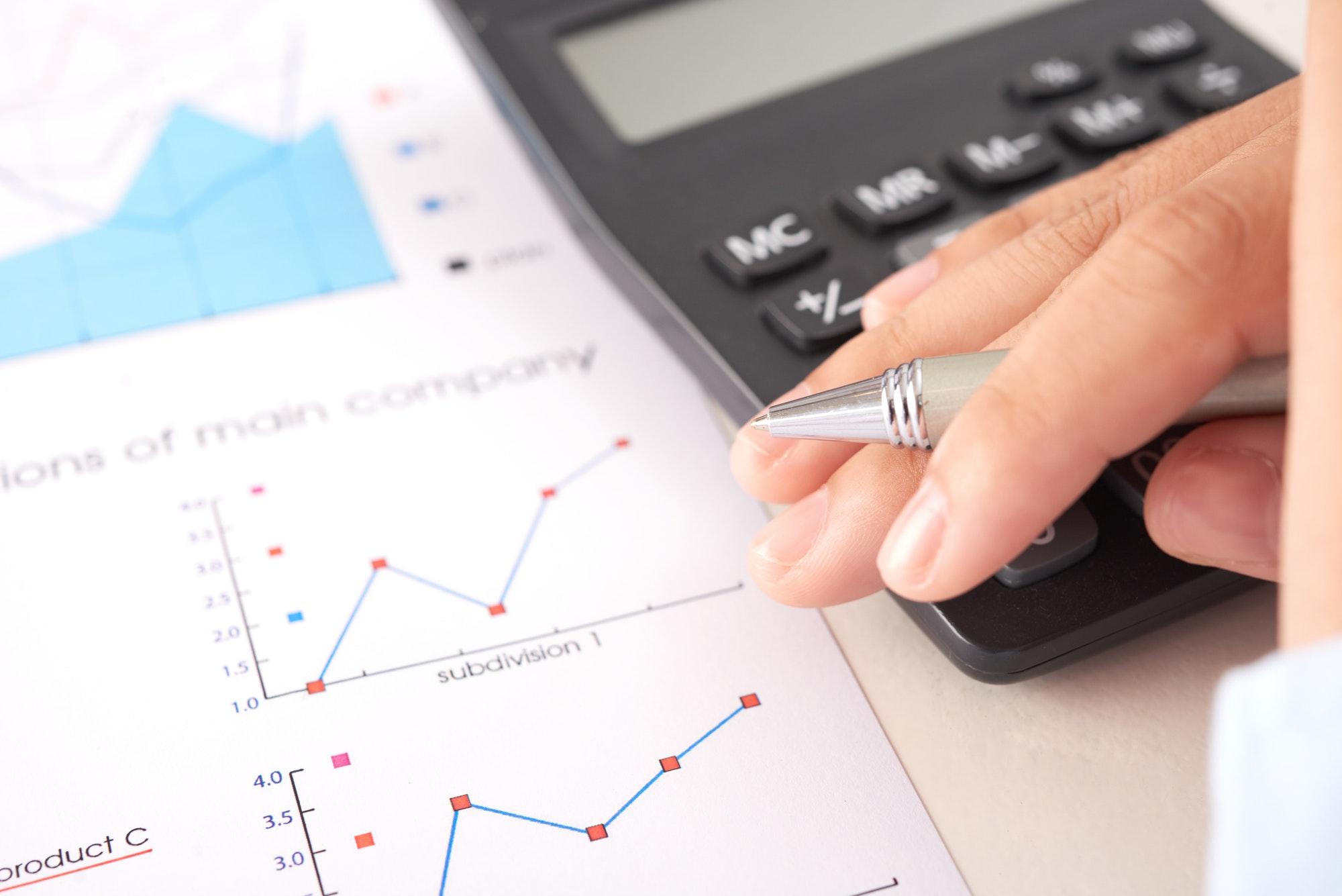 Crop hand near calculator and document